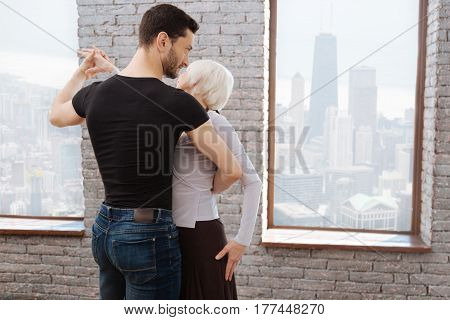 Full of concentration. Skilled confident charismatic man teaching aged woman tango while dancing and showing new dance step