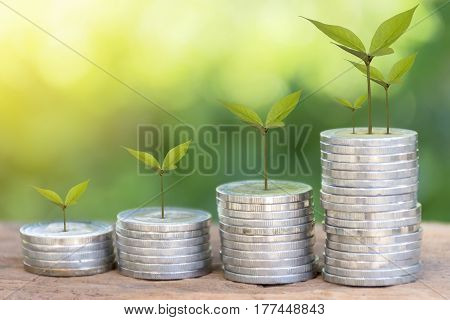 Stacking gold coins on wooden with green background .Business Finance and Money conceptSave money for prepare in the future./productivity growth concept