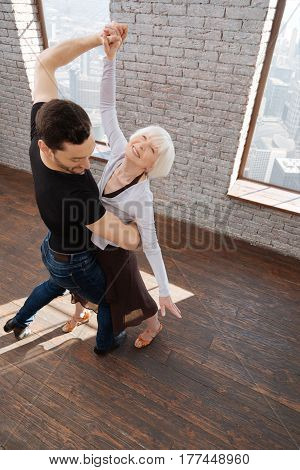 Enjoying dance lesson together. Athletic proficient charismatic dance couch teaching aging woman tango while dancing and showing new dance step