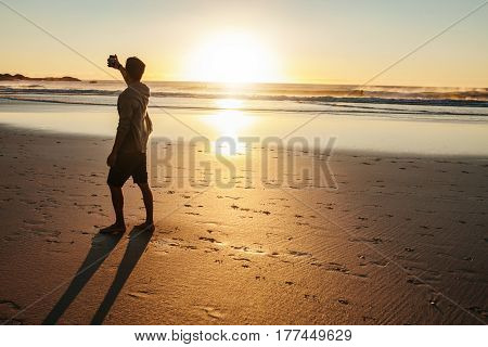 Rear view shot of young man taking selfie at sunset on beach. Man taking self portrait on sea shore.