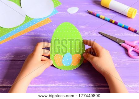 Small child holding a Easter card in hands. Child made Easter greeting card in egg shape. Materials for art creativity on a wooden table. Paper crafts activity in kindergarten or at home