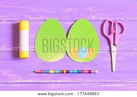How to make Easter egg greeting card. Step. Training. Colored cardboard card in shape of egg, scissors, glue stick, pencil on a wooden table. Children Easter paper craft concept. Top view. Closeup