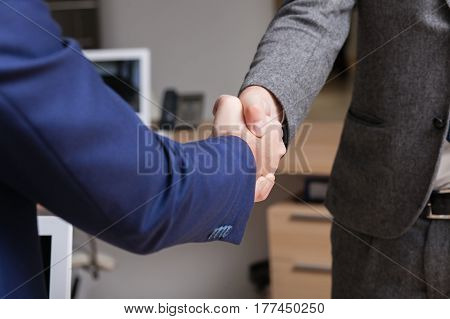 Two men are making handshakein the room