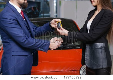 The seller hands over the new car keys to the buyer