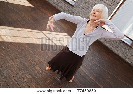 Learning dance of grace . Capable flexible positive aged woman dancing tango in the ballroom while performing dancing steps and showing her grace