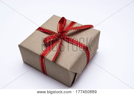 Gift box with gold ribbon on red background