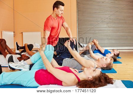 Fitness trainer in pilatess class controls exercise right posture