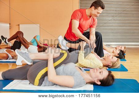 Coach in fitness class showing stretching exercise and helps woman at fitness center