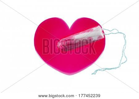 New unused tampon on heart shaped red syrup liquid that looks like blood, isolated on white background