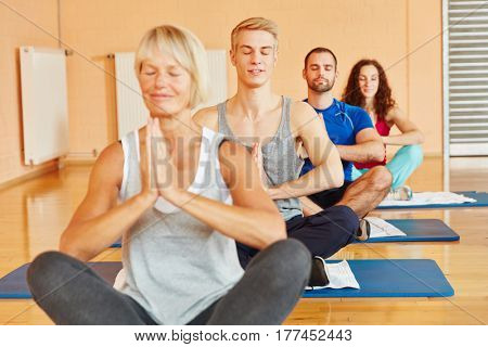 Group meditates and relaxes in yoga class at fitness center