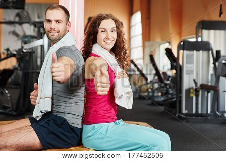 Successful couple at fitness center holding thumbs up