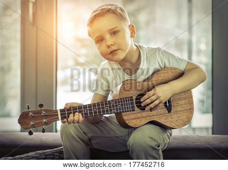 Young boy play on guitar at home at sunny day. Boy play on ukulele - hawaiian guitar.