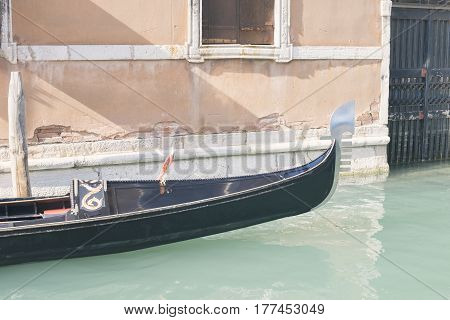Venice gondola passing by narrow channel near yellow building wall