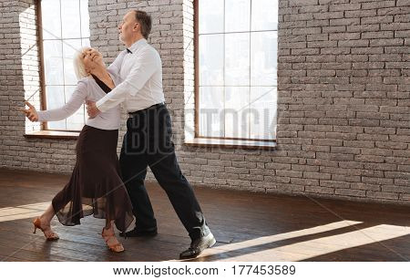 Sharing love with each other. Lovely cute graceful elderly couple performing classical dance in the ballroom while improving dance skills and expressing happiness