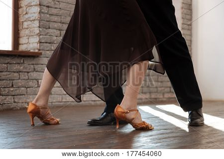Still remember every step. Skillful crafty senior dance couple waltzing in the ballroom while showing dance skills and expressing love