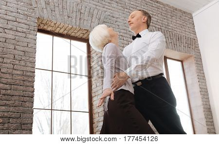 With all my love to you. Cheerful happy senior dance couple waltzing in the ballroom while showing dance skills and expressing love and care