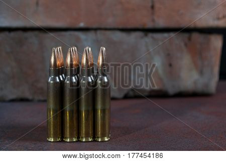 Group of  ammunition geometrically placed in rows on a rusted metal background
