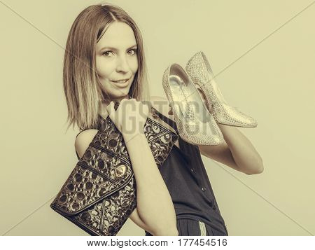 Elegant fashionable woman with leather handbag and high heels. Stylish girl holding black bag and silver shoes. Female fashion vogue. Studio. Sepia filter.