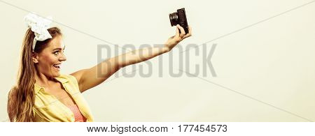 Hobby leisure spending free time. Attractive pin up lady with camera taking pictures. Smiling girl wearing yellow shirt.