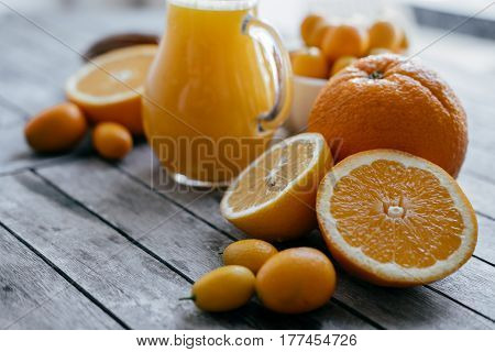 Wooden Board With Kumquat In A White Bowl, Oranges, Lemons And Fresh Juice Squeezer. Space For Text