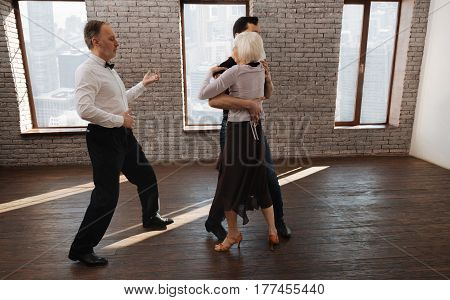 Teaching waltz senior people. Helpful experienced mature dance instructor teaching aged dance couple while having training session and waltzing