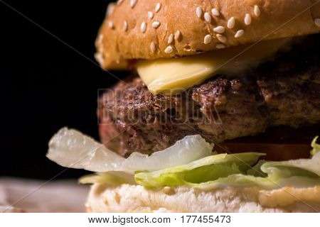 Close-up of a burger. Fresh lettuce and grilled meat. Melted cheddar and juicy beef.