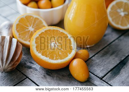 Fresh Kumquat In A White Bowl, Oranges, Lemons And Fresh Juice Squeezer On Wooden Board.