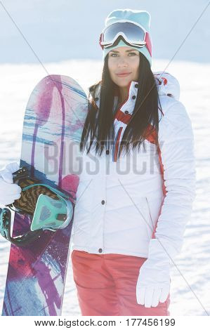 Photo of woman with snowboard on mountain in winter