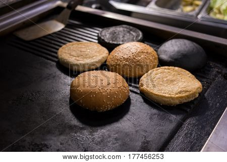 Burger buns with sesame. Baked products on pan.