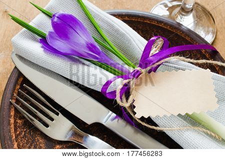 Spring Festive Table Setting With Fresh Flower and Empty Tag. Napkin plate and cutlery on wooden table. Holidays background. Selective Focus.