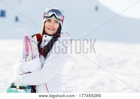 Beautiful brunette on winter mountain holding snowboard