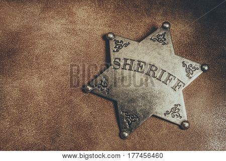 Sheriff badge on brown leather texture background. Macro shot.