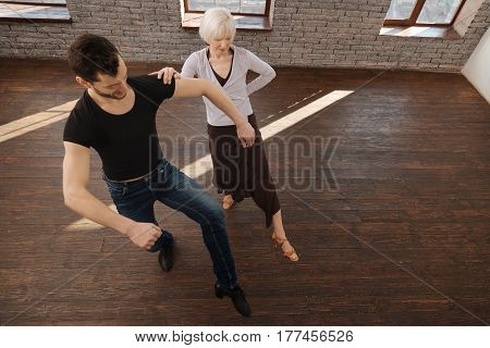 Leading you to the success . Flexible active powerful dance instructor teaching retired woman tango while having training session and performing dance step