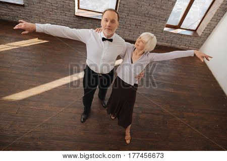 Youthfulness inside us . Gifted smiling satisfied senior dance couple waltzing in the dance studio while showing dance skills and expressing happiness