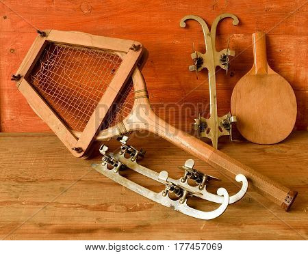 Vintage Ice Skates And Tennis Racket On Wooden Background. Retro Ice Skates And Tennis Racket.