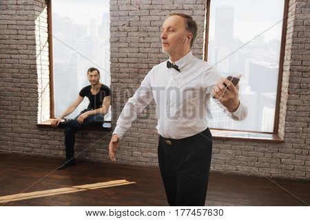 Music all around us . Skilled peaceful diligent retired man dancing waltz and listening to the music while his dance instructor sitting in the background