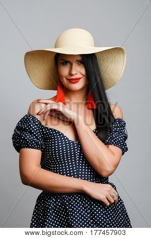 Brunette in dress and hat on blank gray background