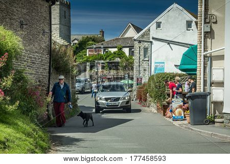 Mortehoe, DEVON, UK - July 14, 2016: Street in the town of Mortehoe. An elderly man goes with a dog. The car stopped - waiting