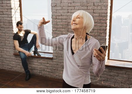 Relishing art inspiration. Happy optimistic cheerful old woman dancing and listening to the music while dance couch sitting in the background