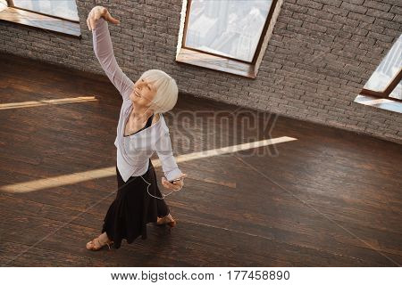 Enjoying my artistic weekend. Lively positive elderly woman dancing waltz and listening to the music while holding the modern gadget
