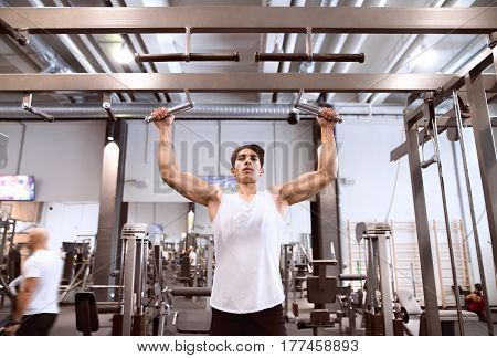 Young hispanic fitness man in gym working out, doing pull-ups on horizontal bar
