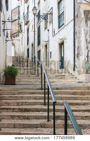 Narrow cobblestone stairs in urban city streets of Lisbon Portugal