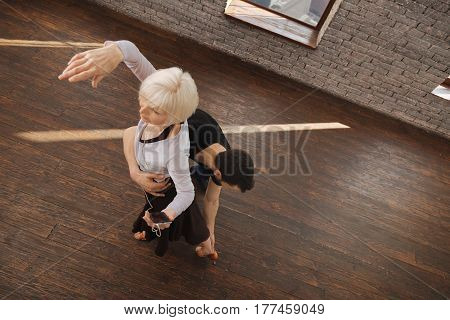 Mastering art step. Professional athletic attentive dance instructor teaching elderly woman salsa while dancing and demonstrating new step