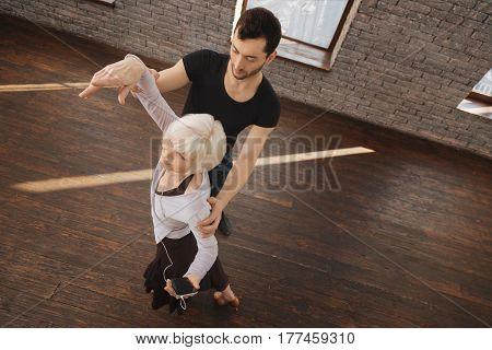 Improving posture together. Proficient athletic skilled dance instructor teaching senior woman while working and demonstrating perfect posture