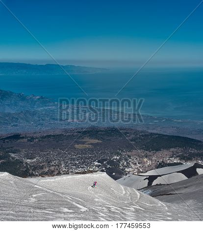 Skiing On The Etna Volcano With The Background Of Taormina Sicilian Sea Coast Of Calabria