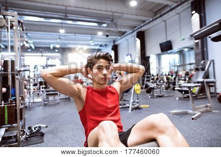 Fit hispanic man doing crunches, exercising abdominal muscles during training in fitness gym.