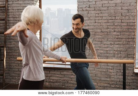 Working diligent for success. Positive charming experienced dancer teaching elderly woman while standing next to the barre and demonstrating right posture
