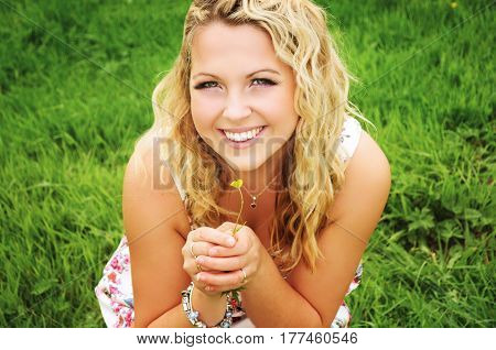 Beautiful smiling young blonde woman with shoulder length curly hair is smelling a small yellow flower on the meadow.