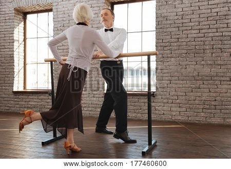 Enjoying our dance class. Positive joyful aging couple dancing in the dance studio while expressing positivity and standing next to the barre