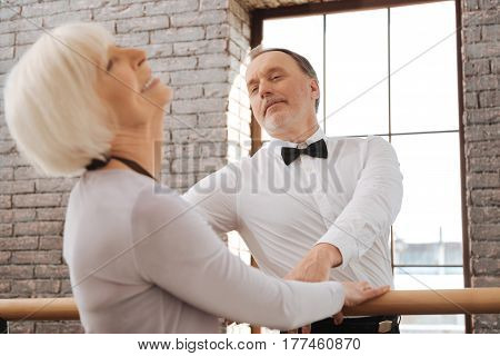 My lovely gentleman. Satisfied optimistic retired couple dancing in the art studio while expressing joy and standing next to the barre